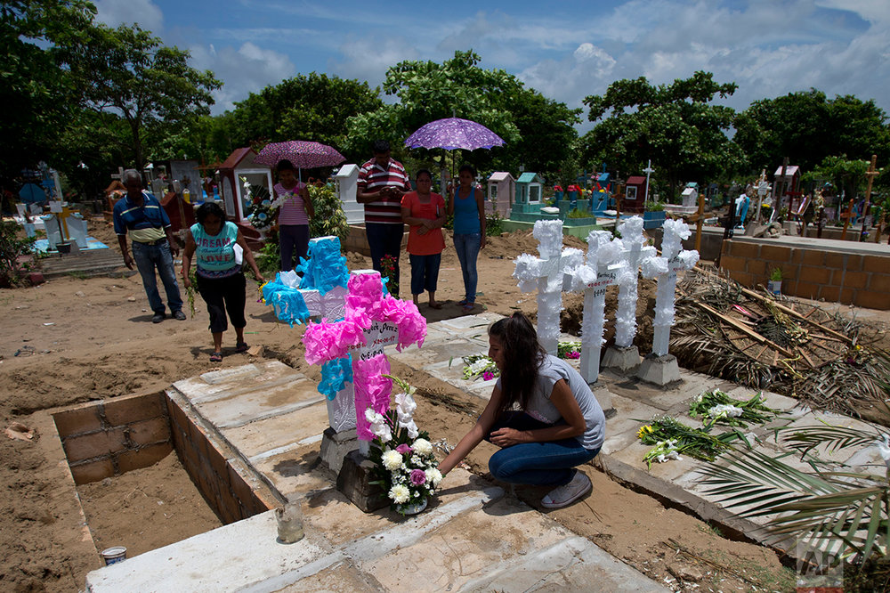 In this July 2, 2017 photo, aunts, uncles and grandparents place flowers and home-made concrete crosses atop the graves of the Martinez children, their mother and father at a cemetery in Coatzacoalcos, Veracruz State, Mexico. (AP Photo/Rebecca Blackwell)