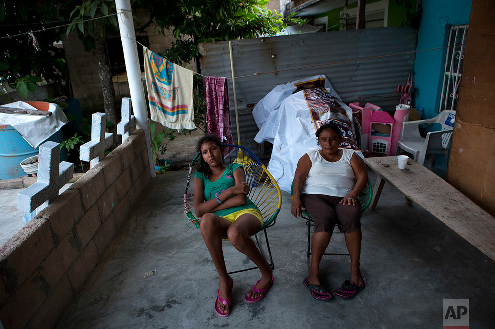 In this July 1, 2017 photo, Flora Martinez, right, grandmother to the murdered Martinez children, sits with one of her daughters on the porch of her home in Coatzacoalcos, Veracruz State, Mexico, as homemade concrete crosses dry.  (AP Photo/Rebecca Blackwell)