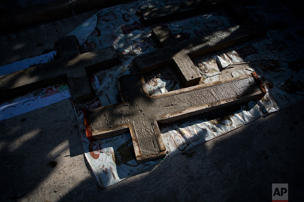 In this June 30, 2017 photo, cement crosses dry inside a mould at the home of Flora Martinez, who lost her son, daughter-in-law, and six young grandchildren when the entire family was executed in Coatzacoalcos, Veracruz State, Mexico. (AP Photo/Rebecca Blackwell)