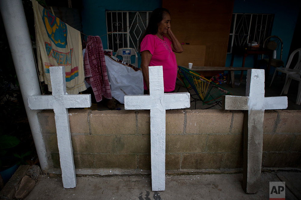 In this July 1, 2017 photo, Isabel Osorio Luna, the great-grandmother of the murdered Martinez children walks past homemade concrete crosses being painted to adorn the simple tombs of the family of six, in Coatzacoalcos, Veracruz State, Mexico. (AP Photo/Rebecca Blackwell)