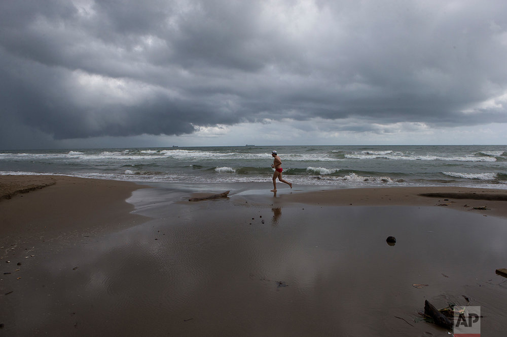 In this July 2, 2017 photo, a man jogs along the beach as storm clouds hang over the Gulf of Mexico in Coatzacoalcos, Veracruz State, Mexico. (AP Photo/Rebecca Blackwell)