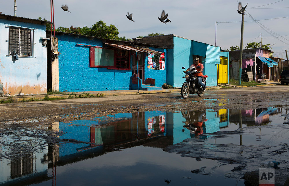 In this June 30, 2017 photo, a man bikes along a street in the Nueva Calzadas neighborhood where a family of six was murdered, in Coatzacoalcos, Veracruz State, Mexico. (AP Photo/Rebecca Blackwell)