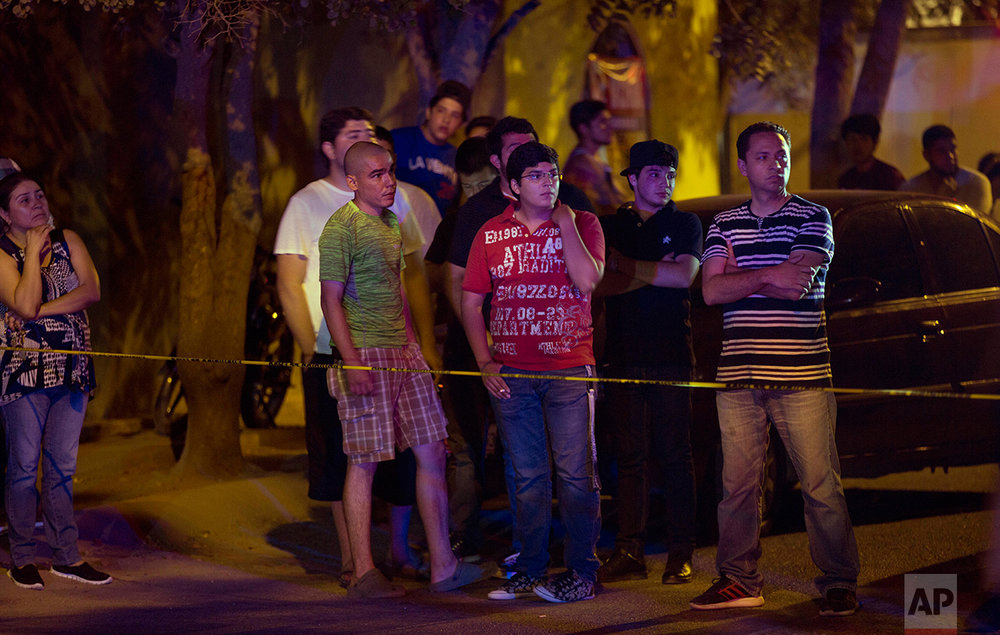 In this  July 1, 2017 photo, bystanders look at the crime scene where three people were shot inside a car in Culiacan, Sinaloa State, Mexico. (AP Photo/Enric Marti)