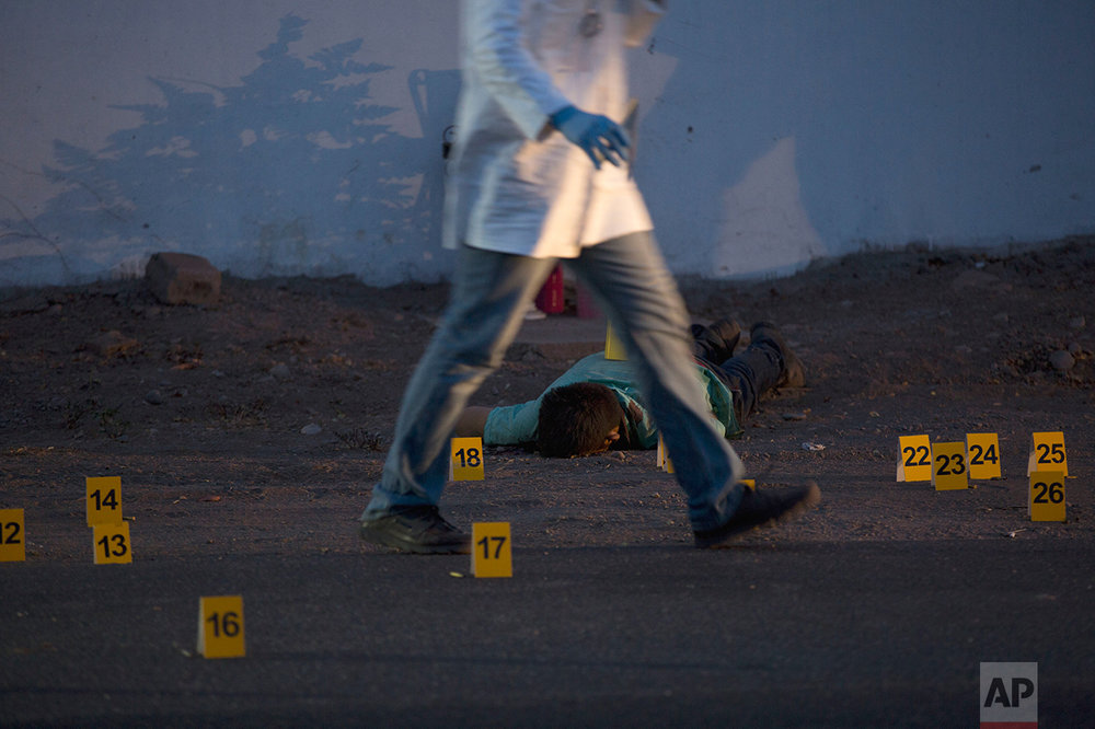 In this June 29, 2017 photo, a police investigator walks past one of three bodies found lying on a road in the town of Navolato, Sinaloa State, Mexico.  (AP Photo/Enric Marti)