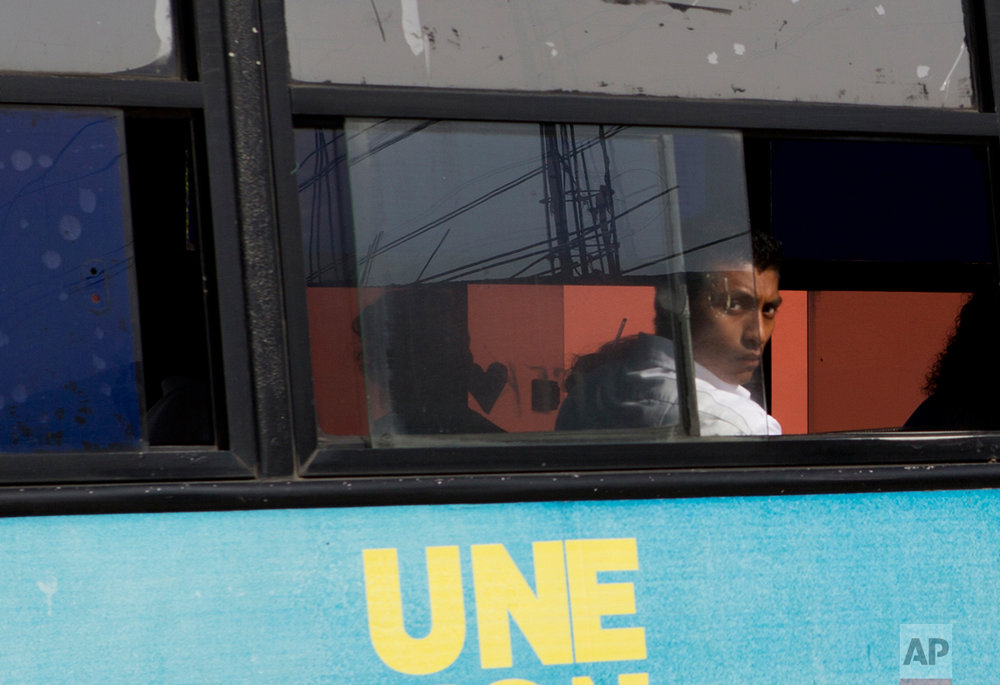 In this June 30, 2017 photo, a man looks out from the window of a public transport bus in the Nueva Calzadas neighborhood where the Martinez family was killed in Coatzacoalcos, Veracruz State, Mexico. (AP Photo/Rebecca Blackwell)
