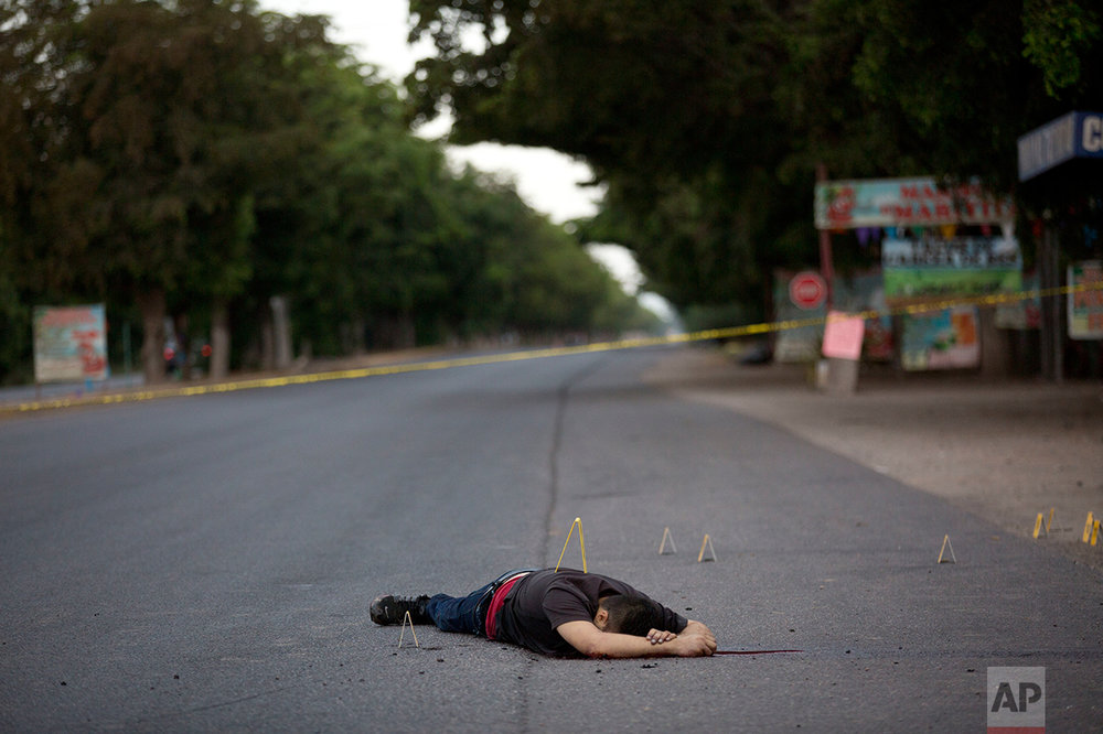 In this early Thursday, June 29, 2017 photo, a man shot earlier lies on a road in the town of Navolato, Sinaloa State, Mexico. 59 AK type and AR-15 casings were found in the area. (AP Photo/Enric Marti)