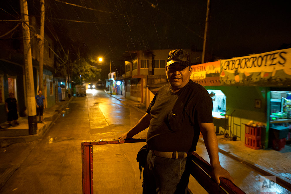 In this July 1, 2017 photo, a Mundo Nuevo neighborhood guard patrols the area on a patrol truck after blocking off two of the three entrances to the isolated district on the outskirts of Coatzacoalcos, Veracruz State, Mexico. After kidnappings for ransom skyrocketed, driving many residents to move away, the local government organized a neighborhood patrol and then began closing off its entry roads at night in January. (AP Photo/Rebecca Blackwell)
