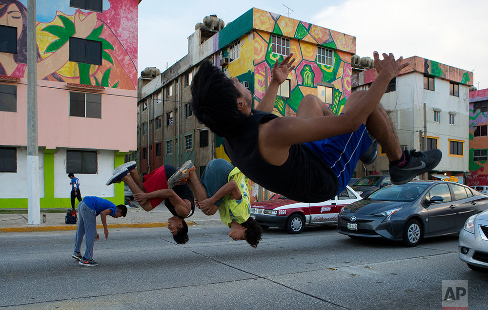 In this June 30, 2017 photo, a group of boys who practice parkour do tricks at a traffic light to earn money from drivers, in Coatzacoalcos, Veracruz State, Mexico. (AP Photo/Rebecca Blackwell)
