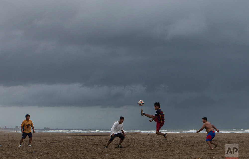 In this July 2, 2017 photo, men play pickup soccer on the Gulf of Mexico waterfront in Coatzacoalcos, Veracruz State, Mexico. (AP Photo/Rebecca Blackwell)