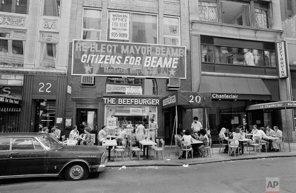 A midtown, Manhattan restaurant moved its tables and customers to the sidewalk, July 14, 1977, after a massive power failure in New York City cut off electricity inside. (AP Photo/Marty Lederhandler)