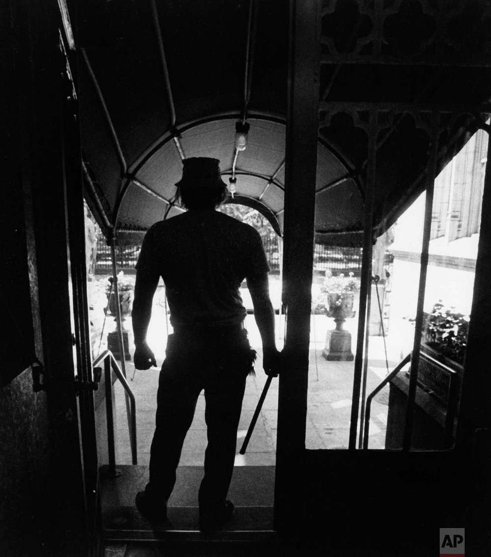 A doorman on New York's Gramercy Park arms himself with a nightstick as a preventative measure following the blackout of New York, July 14, 1977. Looting was continuing in the city Thursday. (AP Photo)