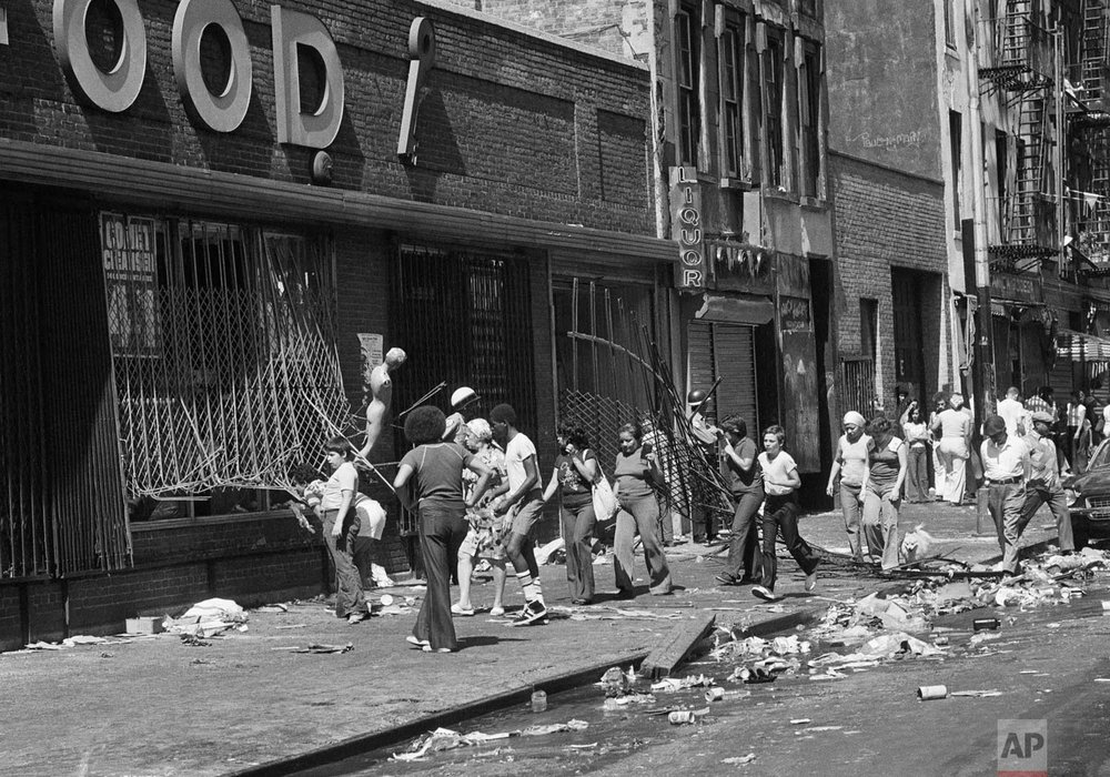 People peer into a looted store on 110th Street at Lexington Ave. in Manhattan the day after the power failure in New York, July 14, 1977.  (AP Photo)