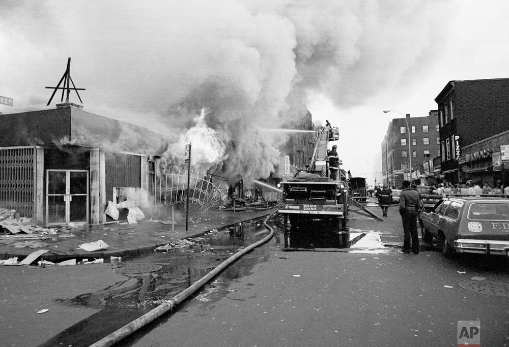 Firemen battle flames at a store in the Bronx borough of New York, one of many fires that broke out during the massive power failure that crippled the city for more than 24 hours, seen July 14, 1977. Firemen answered 1,500 alarms, 400 of which were actual fires. Forty of the fires were termed serious. (AP Photo)