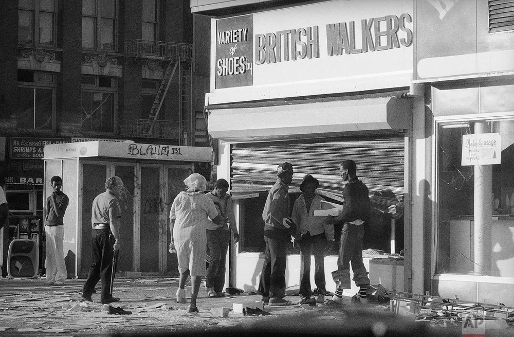 Looters in Manhattan's Harlem section reach past a bent security gate to ransack the window of a shoe store in New York on Thursday, July 14, 1977. A massive power failure in the metropolitan New York area on Wednesday led to acts of vandalism in some parts of the city. New York Mayor Abraham Beame said some 2,000 people were arrested. (AP Photo/Ed Bailey)