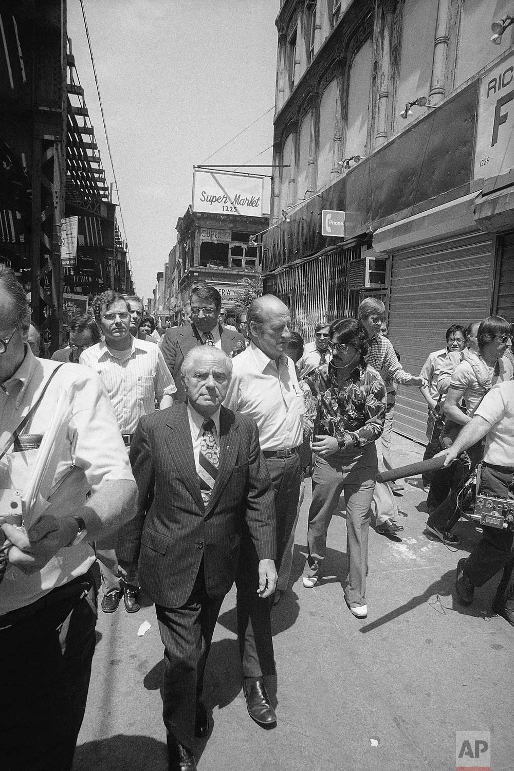 New York Mayor Abraham Beame, center, walks with shopkeepers and newsmen through looter-ravaged areas in New York's Bedford-Stuyvesant district on Friday, July 15, 1977. The area was one of the hardest hit by looters during Wednesday and Thursday's power outage in metropolitan New York City. (AP Photo)