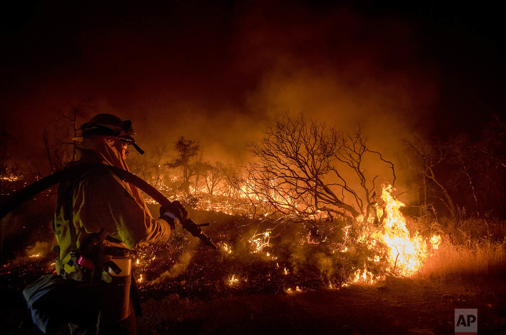 Firefighter Kern Kunst battles the Wall fire near Oroville, Calif., on Saturday, July 8, 2017. According to CalFire, the blaze has scorched 1,000 acres and destroyed 10 homes. (AP Photo/Noah Berger)