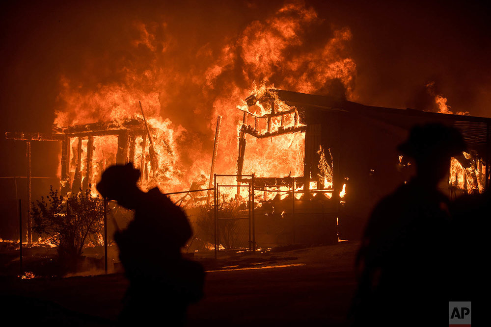 Flames from a wildfire consume a residence near Oroville, Calif., on Sunday, July 9, 2017. Evening winds drove the fire through several neighborhoods leveling homes in its path. (AP Photo/Noah Berger)