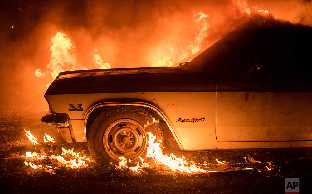 Flames from a wildfire consume a car near Oroville, Calif., on Saturday, July 8, 2017. Evening winds drove the fire through several neighborhoods leveling homes in its path. (AP Photo/Noah Berger)