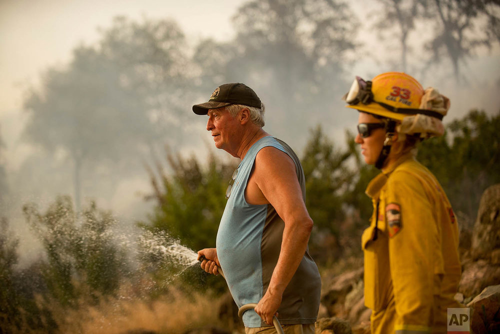Jim Berglund sprays water while defending his home as a wildfire approaches on Saturday, July 8, 2017, near Oroville, Calif.  Although flames leveled Berglund's barn, his home remained unscathed as the main fire head passed. (AP Photo/Noah Berger)