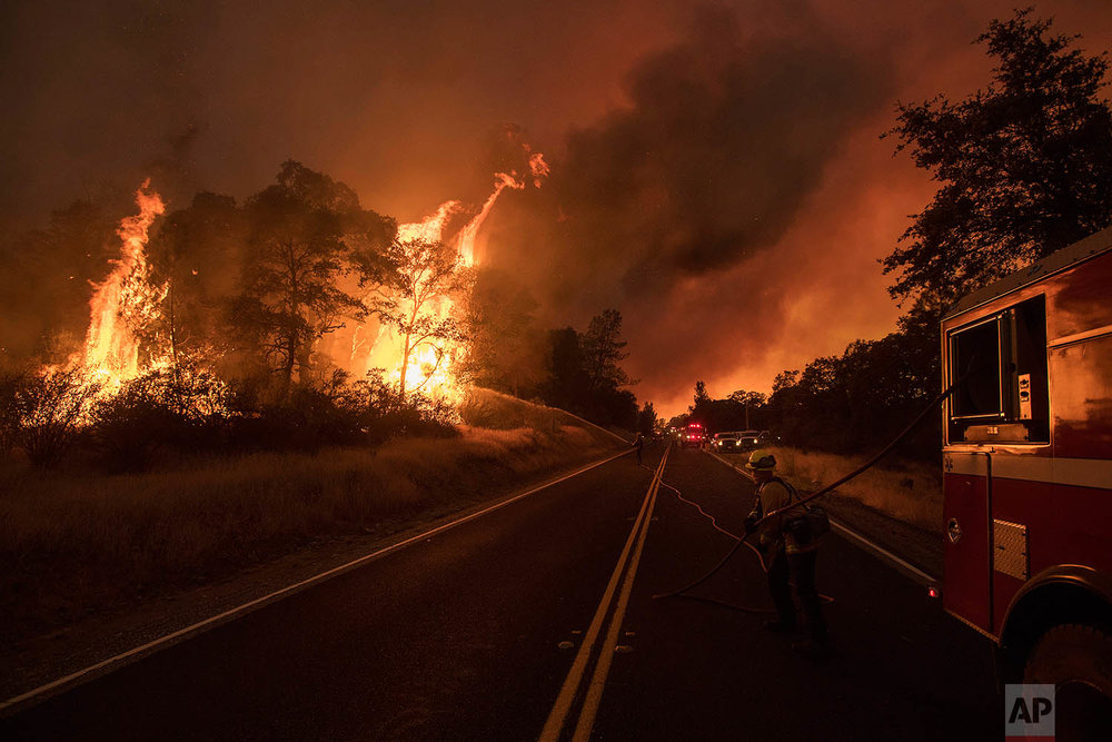 A firefighter battles a wildfire as it threatens to jump a street near Oroville, Calif., on Saturday, July 8, 2017. Evening winds drove the fire through several neighborhoods leveling homes in its path. (AP Photo/Noah Berger)
