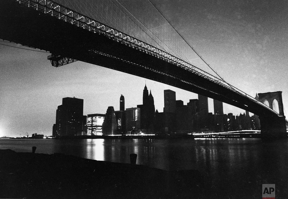 The lights of lower Manhattan are dark as a result of an electrical power failure in this view from under the Brooklyn Bridge on Wednesday, July 13, 1977.  One building at left is lit with emergency power and a stream of light comes from the headlights of moving vehicles on the FDR Drive and on the bridge.  (AP Photo/Ray Stubblebine)