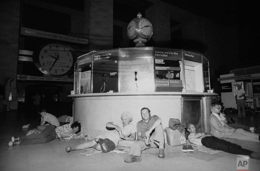 People huddle against the information kiosk in New York's Grand Central Station, Thursday, July 14, 1977 after being stranded by a power failure in the city, its boroughs and some neighboring areas. Grand Central is a crossroad for commuter trains and subways. The clock on the kiosk has the correct time, but the clock at upper left stopped when the power failed on Wednesday. (AP Photo/Steve Oualline)