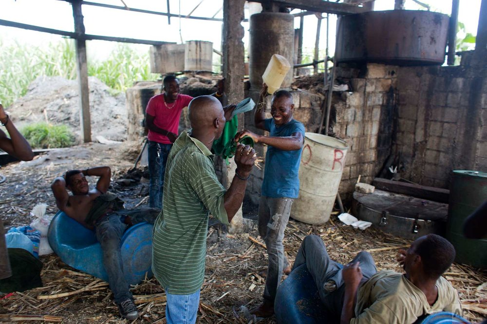 In this June 19, 2017 photo, laborers joke around after working an 8-hour-shift as they drink a recently finished batch of clairin at the Ti Jean distillery where they produce it in Leogane, Haiti. Ti Jean owner Jeanty Bonnefois says his workers make sure they remove the toxic methanol byproduct that occurs during distillation, and his clairin has a good reputation among local consumers. (AP Photo/Dieu Nalio Chery)