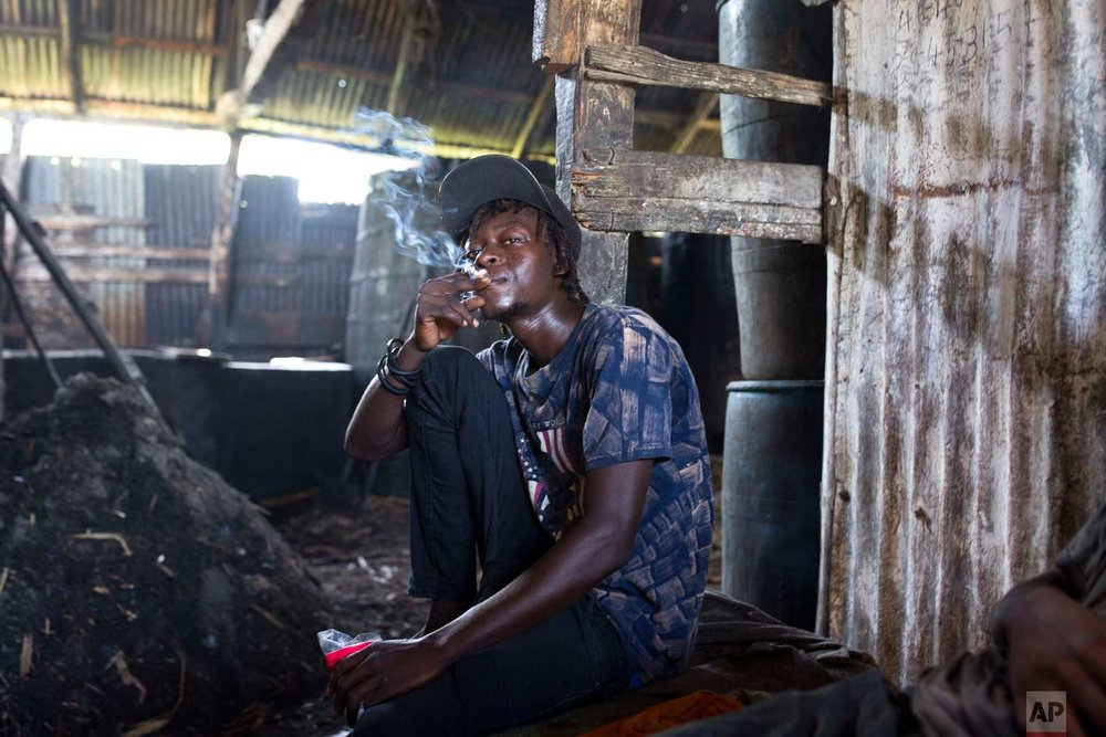 In this June 16, 2017 photo, Beneche Dadou, 20, smokes a cigarette and drinks clairin, a sugar-based alcoholic drink, at the Ti Jean distillery where it's made in Leogane, Haiti, as he takes a break from hauling bagasse, the fiber left over after pressing the juice from the cane. A liter of clairin sells for about $1.36, one-eighth the price of the least expensive bottle of Barbancourt. That price tag makes all the difference in a country where about 60 percent of the population gets by on less than $2 a day. (AP Photo/Dieu Nalio Chery)