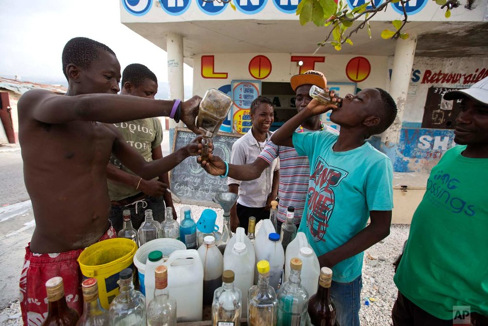 Metelus Obnes pours clairin for a client as Deluson Michel, 15, drinks a small bottle of the sugar-based alcoholic drink in the Cite Soleil area of Port-au-Prince, Haiti, Tuesday, July 11, 2017. A liter of clairin sells for about $1.36, a price tag that makes all the difference in a country where about 60 percent of the population gets by on less than $2 a day. (AP Photo/Dieu Nalio Chery)