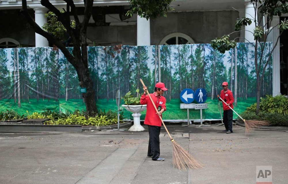 In this Wednesday, Oct. 26, 2016 photo, workers sweep dry leaves against the background of banners depicting a forest used to cover a construction site in Jakarta, Indonesia. One of the strange sights in Indonesia, an ecologically rich archipelago of more than 13,000 islands, is its capital's fondness for fake greenery at a time when the country is known for cutting down its precious tropical forests at a record rate. (AP Photo/Dita Alangkara)