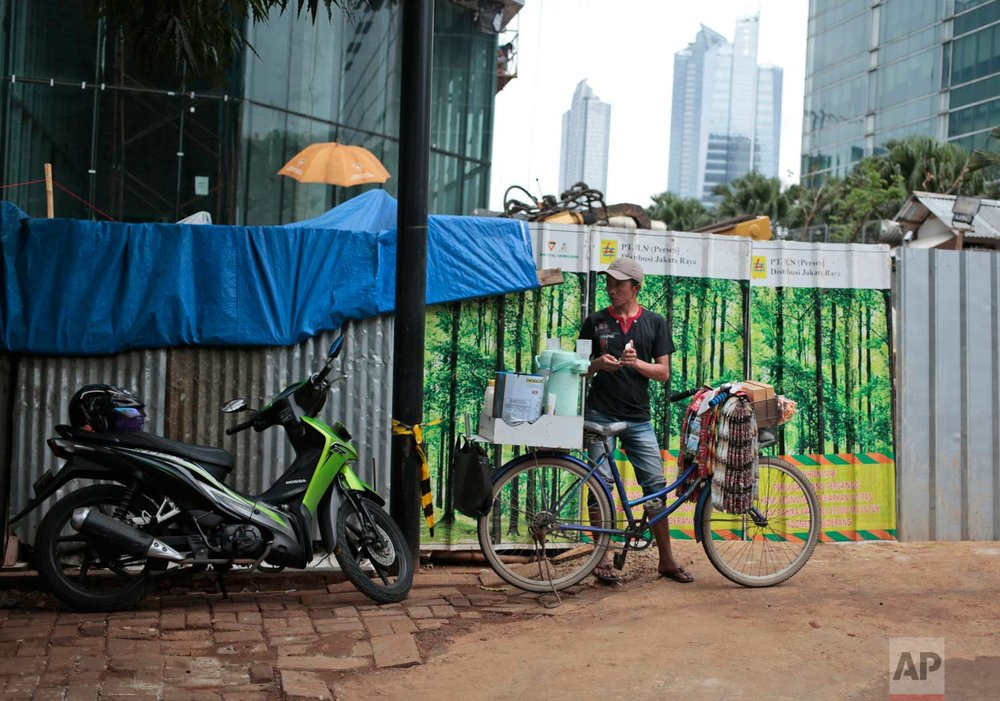 In this Friday, Oct. 14, 2016 photo, a coffee vendor waits for customers near a patch of metal sheets adorned with stickers depicting a forest used to cover a construction site in Jakarta, Indonesia. The capital's fondness for fake greenery creates a n irony as the country is known for cutting down its precious tropical forests at a record rate. (AP Photo/Dita Alangkara)