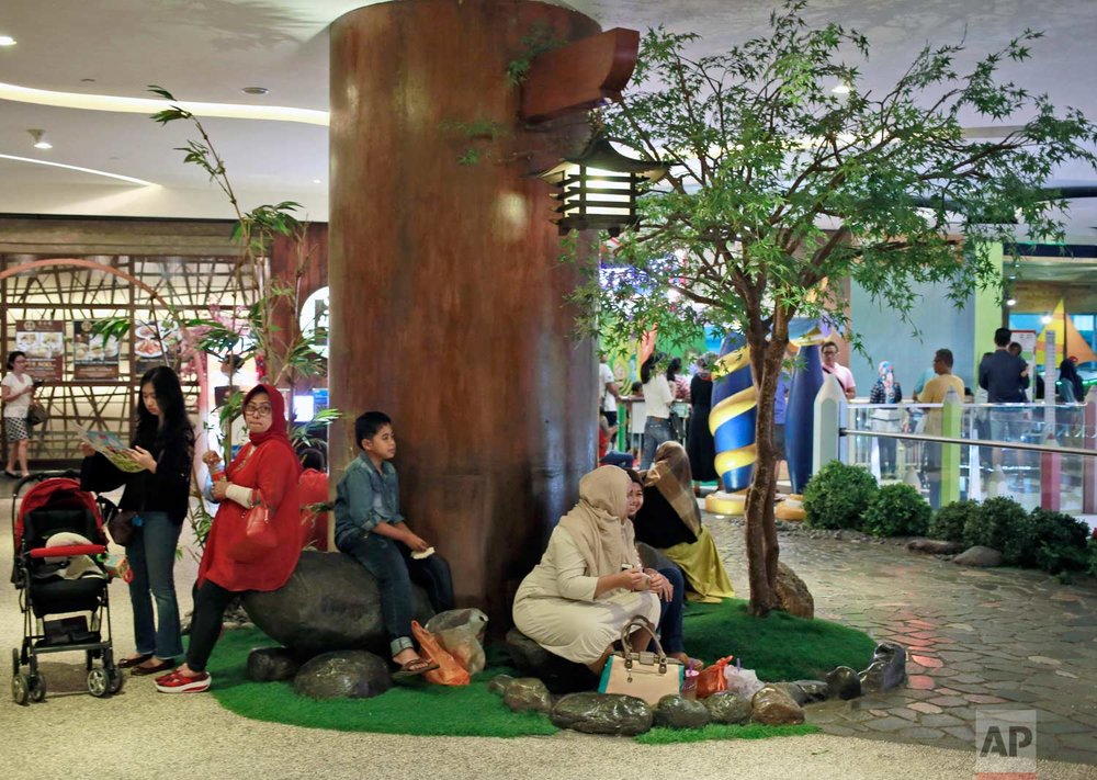 In this Tuesday, March 28, 2017 photo, shoppers take a break under artificial trees at a shopping mall in Jakarta, Indonesia. The metropolitan's gleaming air conditioned malls have a particular fondness for fake trees and forests, creating an irony as the country is known for cutting down its precious tropical forests at a record rate. (AP Photo/Dita Alangkara)