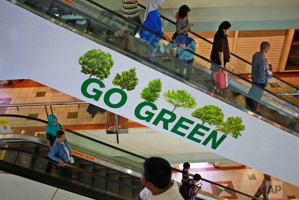 In this Saturday, April 15, 2017 photo, people take an escalator adorned with environmental awareness message at a shopping mall in Jakarta, Indonesia. One of the strange sights in Indonesia, an ecologically rich archipelago of more than 13,000 islands, is its capital's fondness for fake greenery at a time when the country is known for cutting down its precious tropical forests at a record rate. (AP Photo/Dita Alangkara)