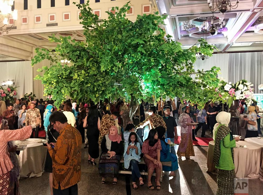 In this Sunday, April 16, 2017 photo, guests sit under an artificial tree during a wedding party in Jakarta, Indonesia. One of the strange sights in Indonesia, an ecologically rich archipelago of more than 13,000 islands, is its capital's fondness for fake greenery at a time when the country is known for cutting down its precious tropical forests at a record rate. (AP Photo/Dita Alangkara)
