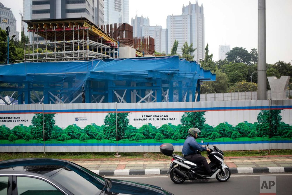 In this Thursday, Nov. 10, 2016 photo, a motorist rides past a construction site covered with metal sheets decorated with large stickers depicting greeneries at the main business district in Jakarta, Indonesia. One of the strange sights in Indonesia, an ecologically rich archipelago of more than 13,000 islands, is its capital's fondness for fake greenery at a time when the country is known for cutting down its precious tropical forests at a record rate. (AP Photo/Dita Alangkara)