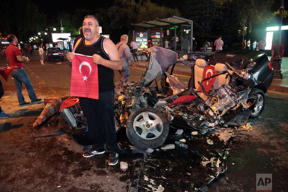 A man poses in front of a damaged car crushed by a military tank as people gather in Ankara's main Kizilay Square to protest the coup. (AP Photo/Burhan Ozbilici)
