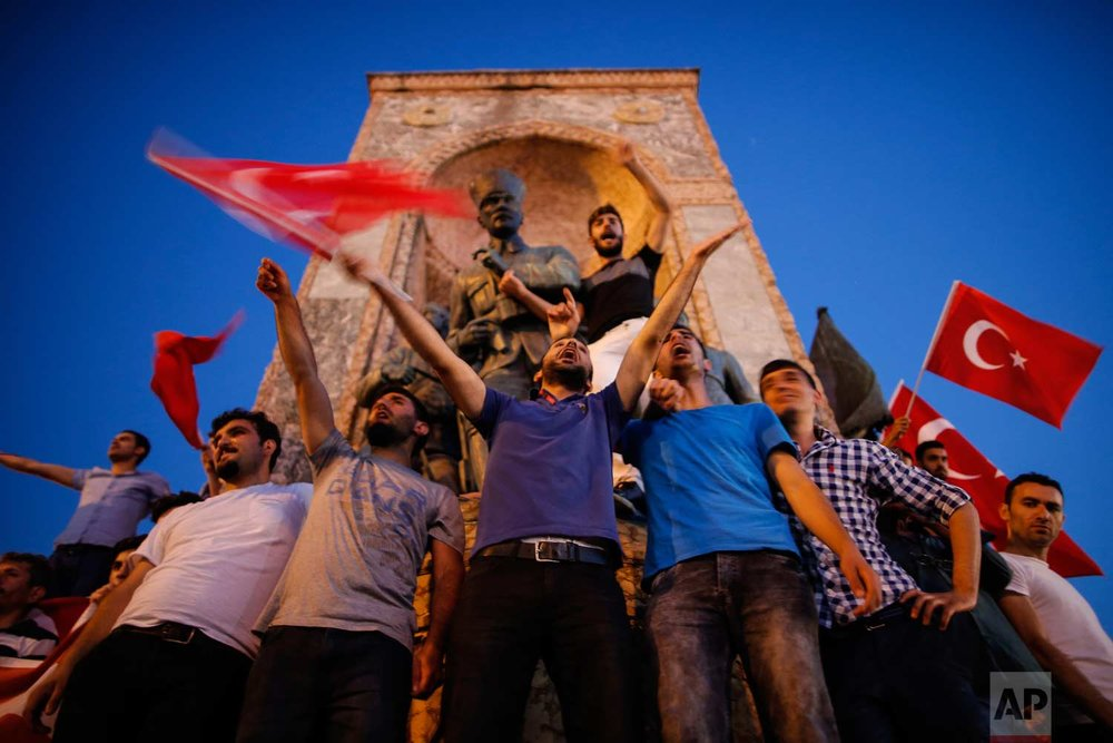People wave Turkish flags as they gather at a pro-government rally in Istanbul's Taksim square. (AP Photo/Emrah Gurel)