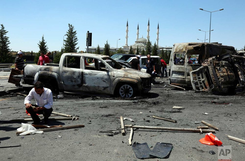 People in Ankara walk next to cars destroyed during the coup. (AP Photo/Ali Unal)
