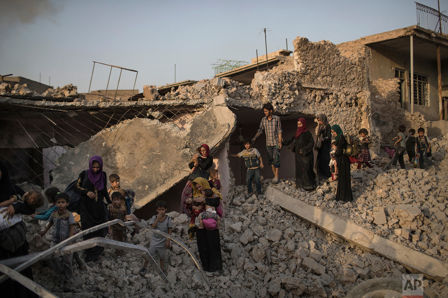 In this July 4, 2017 photo, Iraqi civilians flee fighting between Iraqi forces and Islamic State militants through the rubble of destroyed houses in the Old City of Mosul, Iraq. (AP Photo/Felipe Dana)