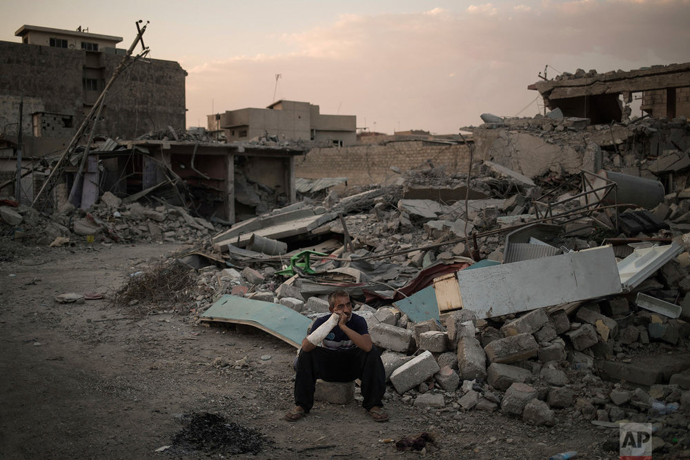 In this July 13, 2017 photo, Saddam Salih Ahmed, who was injured when his house was hit by an explosion, sits on his damaged street in the west side of Mosul, Iraq. (AP Photo/Felipe Dana)