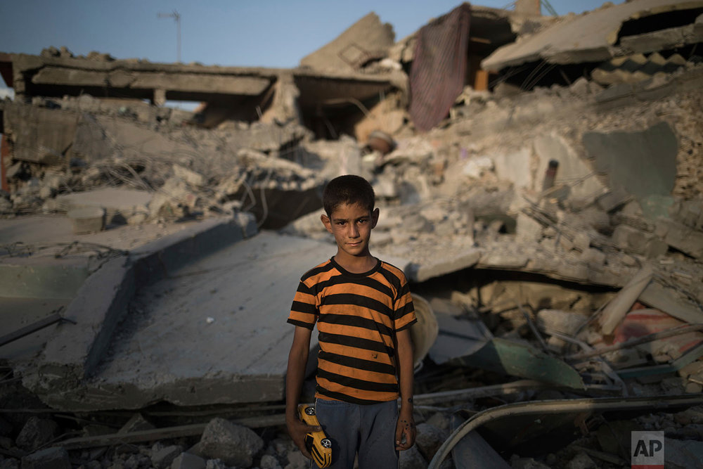 In this July 13, 2017 photo, Ali Mahdi, 9, poses for a photo while playing on his damaged street in the west side of Mosul, Iraq. (AP Photo/Felipe Dana)
