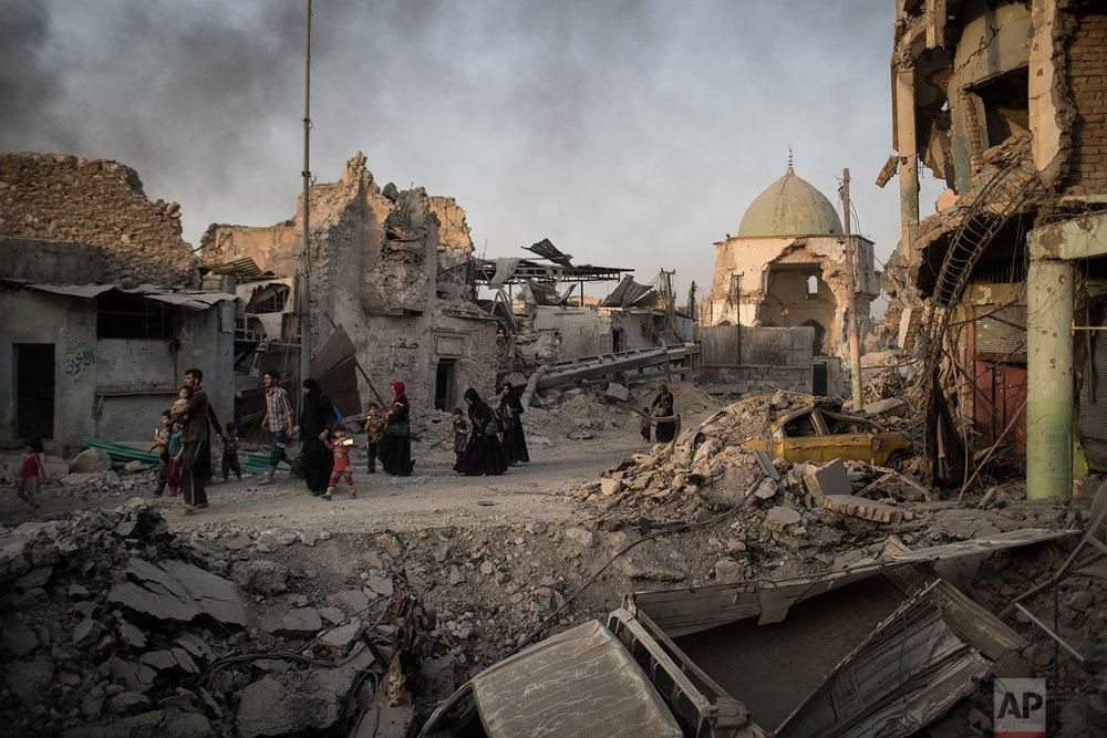 In this July 4, 2017 photo, fleeing Iraqi civilians walk past the heavily damaged al-Nuri mosque during fights between Iraqi security forces and Islamic State militants in the Old City of Mosul, Iraq. (AP Photo/Felipe Dana)