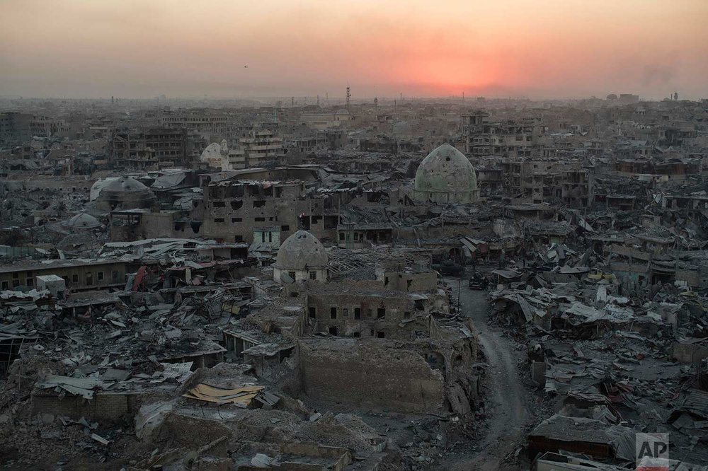 The sun sets behind destroyed buildings in the west side of Mosul, Iraq on Tuesday, July 11, 2017. The 9-month fight to defeat the Islamic State group in Mosul ended in a crescendo of bombardment that damaged or destroyed a third of its historic Old City in just three weeks. (AP Photo/Felipe Dana)