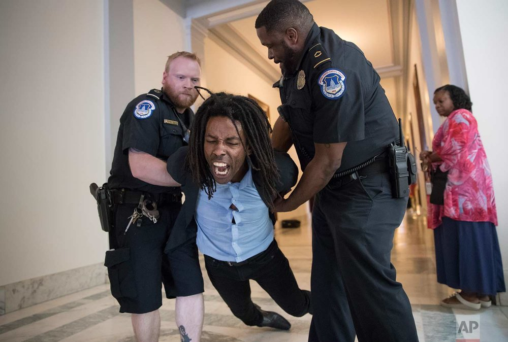 A demonstrator is taken into custody by U.S. Capitol Police as activists protest against the Republican health care bill outside the offices of Sen. Jeff Flake, R-Ariz., and Sen. Ted Cruz, R-Texas, Monday, July 10, 2017, on Capitol Hill in Washington. (AP Photo/J. Scott Applewhite)