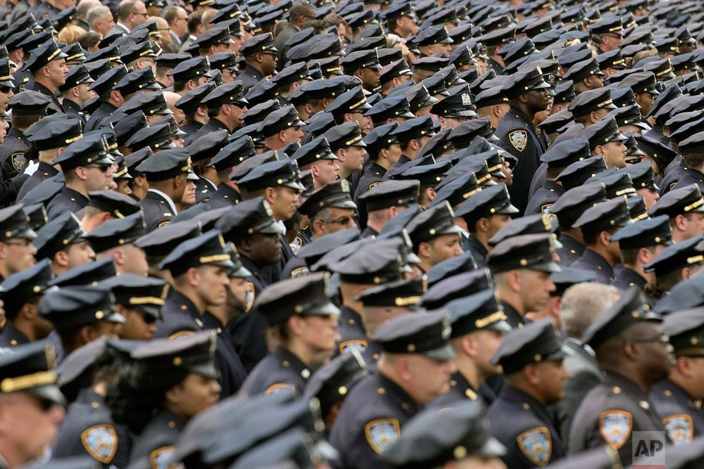 Police officers stand at attention as the funeral procession for slain police officer Miosotis Familia leaves at the World Changers Church after her funeral service, Tuesday, July 11, 2017, in the Bronx borough of New York. Officer Familia was ambushed and killed in a parked police vehicle. (AP Photo/Mary Altaffer)