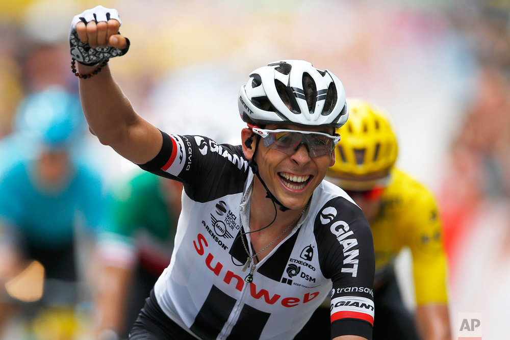France's Warren Barguil clenches his fist as he crosses the finish line, thinking he won the sprint but Colombia's Rigoberto Uran finished ahead of him to win the ninth stage of the Tour de France cycling race over 181.5 kilometers (112.8 miles) with start in Nantua and finish in Chambery, France, Sunday, July 9, 2017. (AP Photo/Peter Dejong)