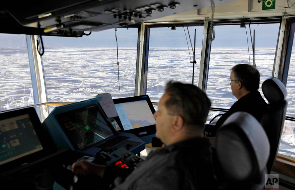 Master Mariner Jyri Viljanen, left, captain of the Finnish icebreaker MSV Nordica and Chief Officer Harri Venalainen, navigate from the bridge through ice floating on the Chukchi Sea off the coast of Alaska while traversing the Arctic's Northwest Passage, Sunday, July 16, 2017. More than a century has passed since the first successful transit of the treacherous, ice-bound Northwest Passage by Norwegian explorer Roald Amundsen in 1906. (AP Photo/David Goldman)