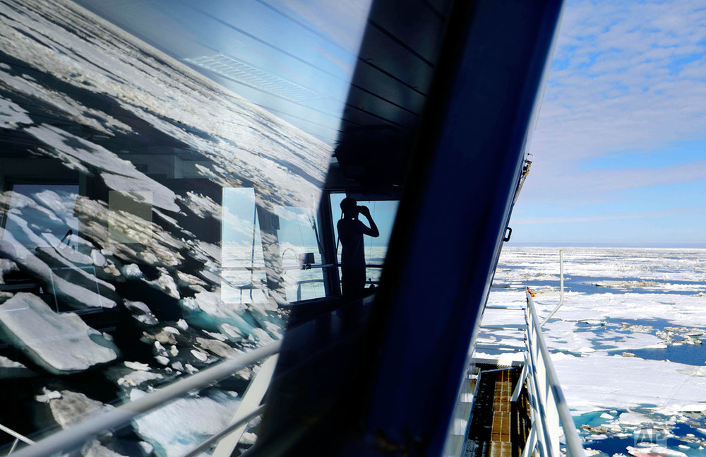 Trainee David Kullualik, of Iqaluit, Nunavut, of Canada's northern territories, looks through binoculars from the bridge of the Finnish icebreaker MSV Nordica as it sails through ice floating on the Chukchi Sea off the coast of Alaska while traversing the Arctic's Northwest Passage, Sunday, July 16, 2017. (AP Photo/David Goldman)