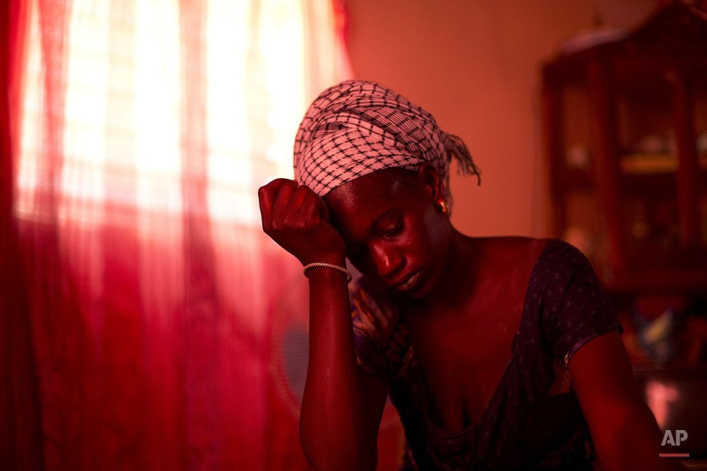 In this Oct. 10, 2013 photo, Aida Diallo, whose ten-year-old son Bamba was killed when a fire struck the Dakar shack where he was sleeping along with other Quranic students, sits in her one-room home in the village of Ndame, Senegal. Bamba's older brother Cheikhou, 13, managed to escape the fire which killed Bamba and three of their cousins. For now the surviving boys and their teacher are back in Ndame, but, says Diallo, when their teacher, her brother, returns to Dakar, Cheikhou will go too. (AP Photo/Rebecca Blackwell)