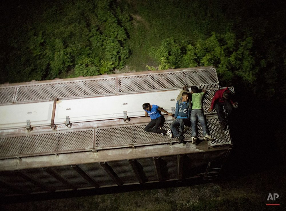 "In this Aug. 26, 2014 photo, Central American migrants rest atop the last boxcar of a moving freight train as it heads north from Arriaga toward Chahuites, Mexico. A Mexican crackdown seems to be keeping women and children off the deadly train, known as ""The Beast,"" that has traditionally helped thousands of migrants head north. The once-open route to the United States has become so difficult that trains now carry a small fraction of the migrants they used to, and almost exclusively adult men. (AP Photo/Rebecca Blackwell)"